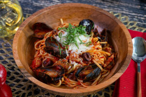 A wooden bowl of Spicy Pasta Alla Diavola with Mussels